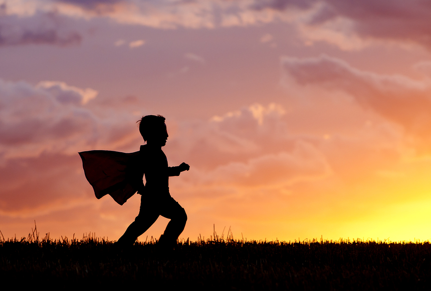 Boy plays super hero at sunset.