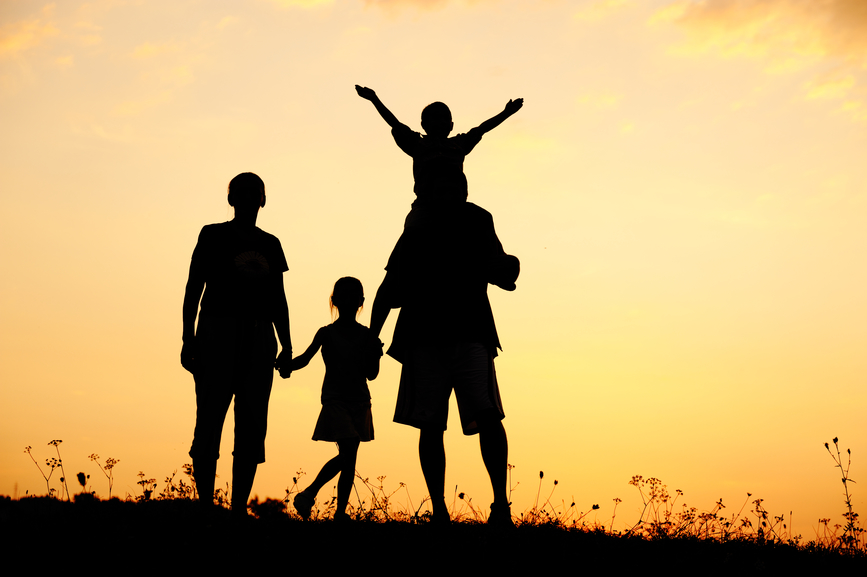 Happy family on meadow at summer sunset